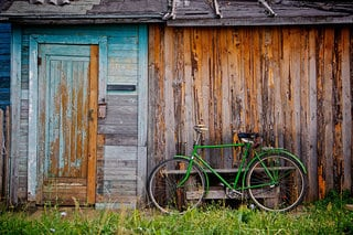 A stock image of a bicycle parked next to a garage.