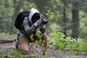 A picture of a man taking a picture with a DSLR camera in a forest.