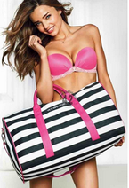 A pictur eof a women in a bikini holding a beach bag.