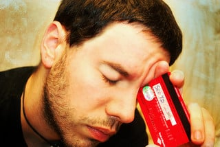 A picture of a man looking frustrated while holding his credit card.