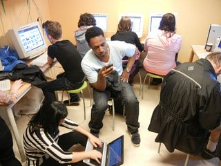 A picture of group of students working on computers and phones.