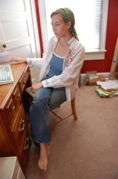 A picture of a woman at home sitting a desk