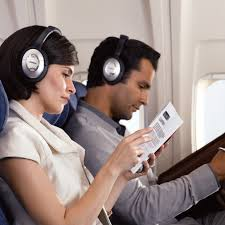 An image showing two people on an airplane with noise-canceling headphones.