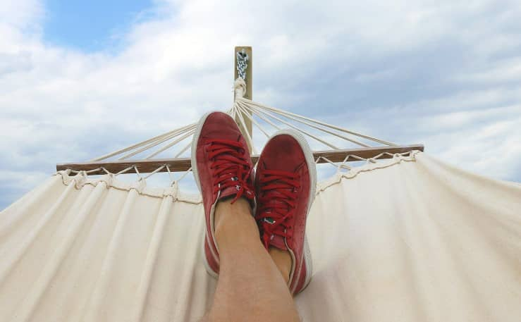 feet kicked up on a hammock with blue sky in background