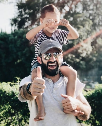 a man giving thumbs up with his son on his shoulders